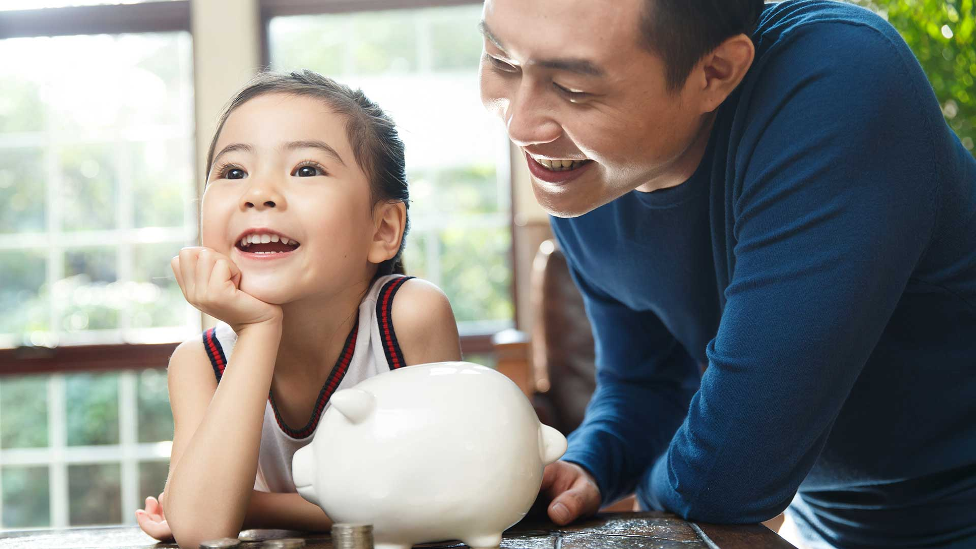 father ,daughter and piggy bank; the image used for wealth education