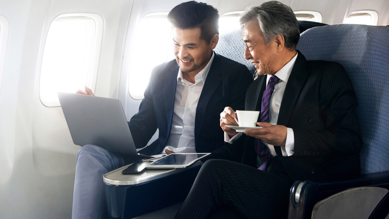Businessmen talking on the plane; the image used for family protection and legacy planning