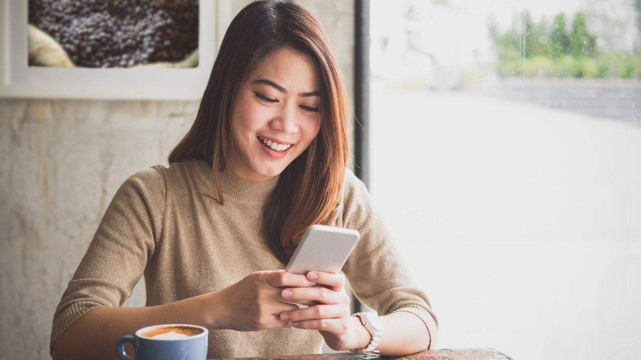 Girl looking at mobile phone in coffee shop; the image used for live within your means